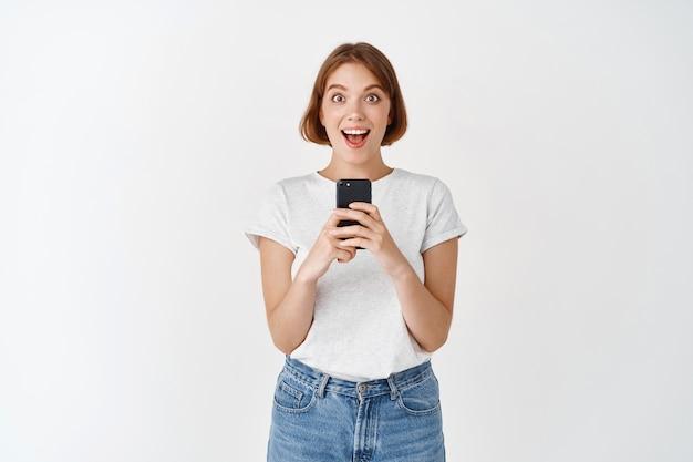 Opgewonden mooi meisje schreeuwt van vreugde na het lezen van een telefoonbericht, het vasthouden van een smartphone en kijken verbaasd, het bekijken van online promo, witte muur