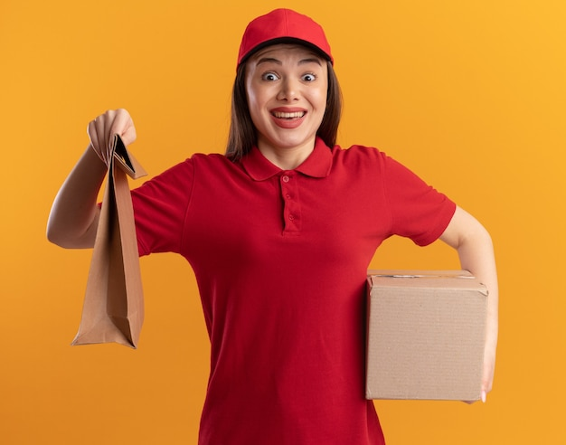 Opgewonden mooie bezorger in uniform houdt papieren pakket en kartonnen doos vast