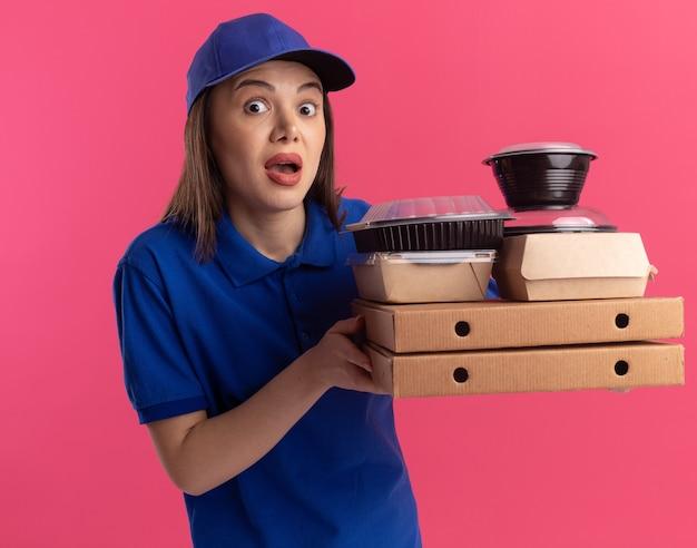Opgewonden mooie bezorger in uniform houdt voedselpakket en containers op pizzadozen en geïsoleerd op roze muur met kopieerruimte