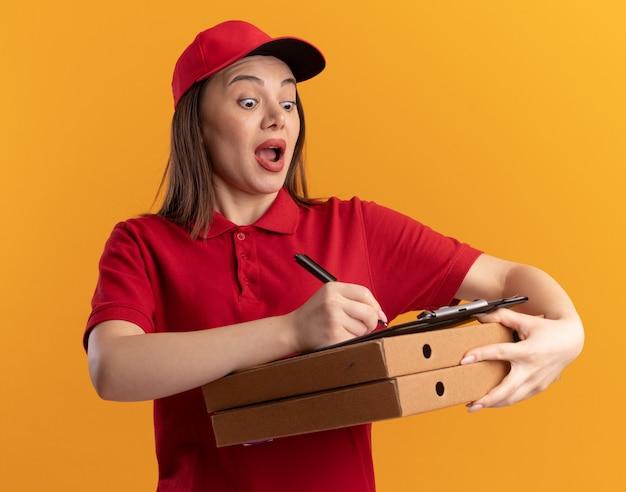 Opgewonden mooie bezorger in uniform schrijft op het klembord met een marker die pizzadozen vasthoudt die op een oranje muur zijn geïsoleerd met kopieerruimte