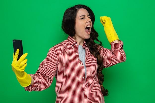 Opgewonden mooie blanke schonere vrouw met rubberen handschoenen die de telefoon vasthoudt en de vuist opheft terwijl ze met gesloten ogen staat