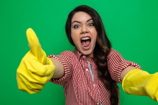 Opgewonden mooie blanke schonere vrouw met rubberen handschoenen die naar voren kijkt en omhoog kijkt
