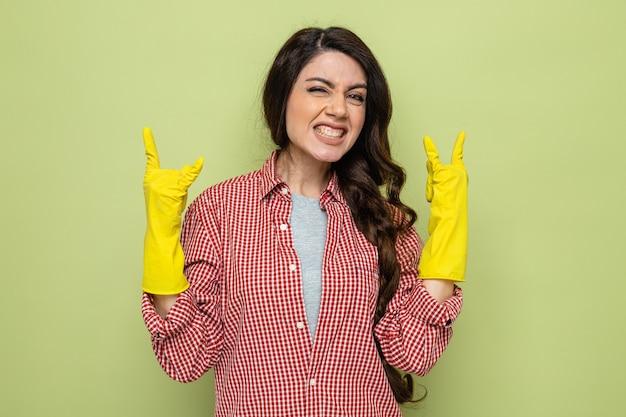 Opgewonden mooie blanke schonere vrouw met rubberen handschoenen gebaren hoorns teken