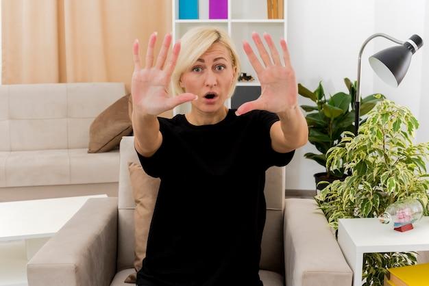 Opgewonden mooie blonde russische vrouw zit op fauteuil, gebaren tien met vingers in de woonkamer