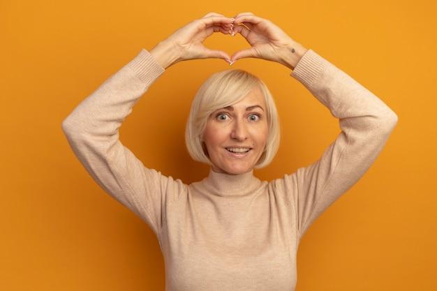 Opgewonden mooie blonde slavische vrouw gebaren hart handteken boven het hoofd op oranje