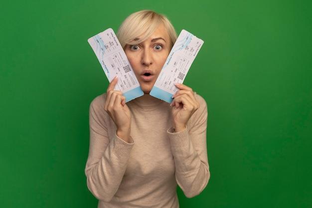 Opgewonden mooie blonde slavische vrouw houdt vliegtickets dicht bij het hoofd op groen