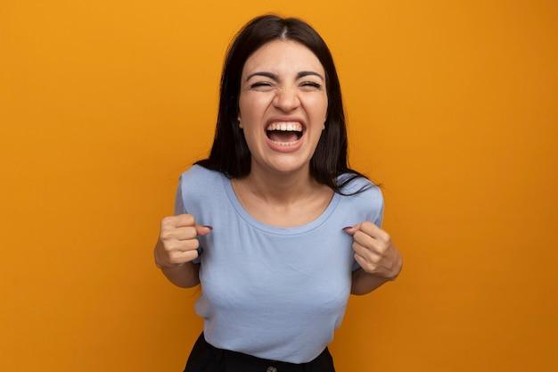 Opgewonden mooie brunette vrouw houdt vuisten geïsoleerd op oranje muur