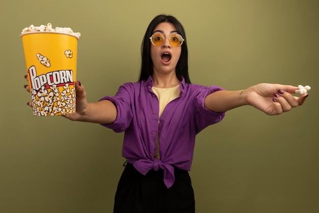 Opgewonden mooie brunette vrouw in zonnebril houdt emmer popcorn geïsoleerd op olijfgroene muur