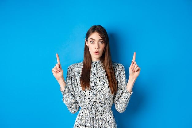 Opgewonden mooie dame in jurk zegt wow, kijkt geïntrigeerd door advertentie, wijst met de vingers naar het logo, staat tegen blauw.