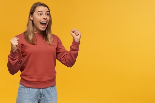 Opgewonden mooie jonge vrouw in vrijetijdskleding toont winnaargebaar met zowel opgeheven handen als vuisten en schreeuwen over gele muur