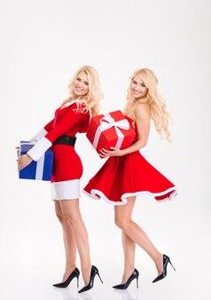Opgewonden mooie jonge zusters tweeling in rode kerstman kostuums dansen met huidige dozen op witte achtergrond boxes