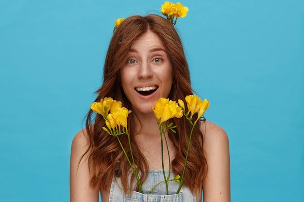Opgewonden mooie jongedame met natuurlijke make-up verbaasd wenkbrauwen optrekken terwijl ze vreugdevol naar de camera kijkt, staande over de blauwe achtergrond met gele freesia