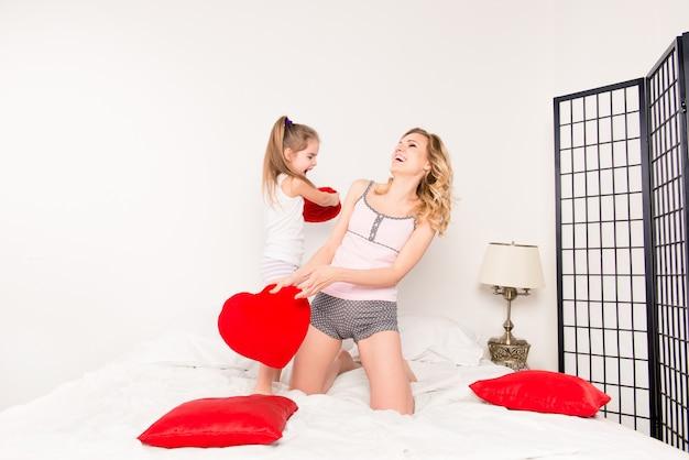Opgewonden mooie moeder en dochter vechten met kussens in de slaapkamer