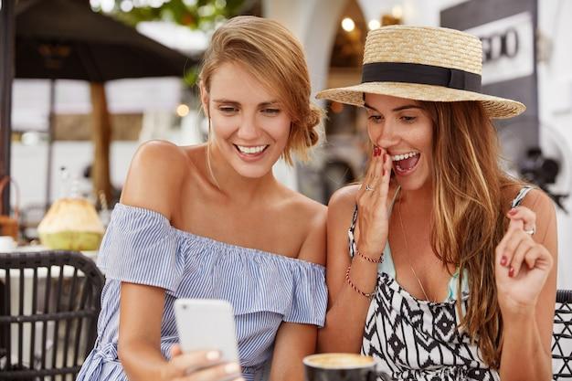 Opgewonden mooie twee vrouwen kijken naar grappige video op moderne mobiele telefoon, hebben verbaasde en blije uitdrukkingen, besteden gratis tijd aan een terrasje, verbonden met supersnel internet.