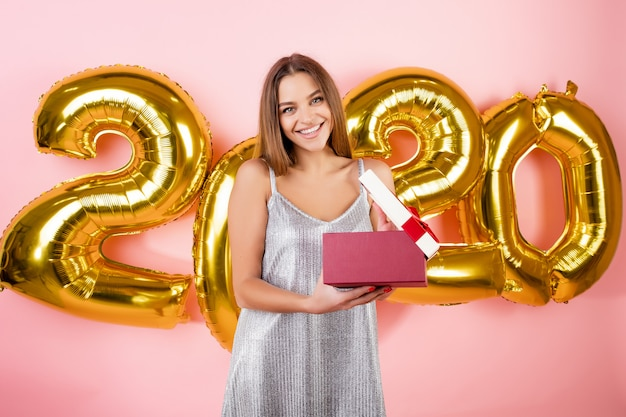 Opgewonden mooie vrouw cadeau doos openen voor nieuwjaar 2020 ballonnen geïsoleerd over roze