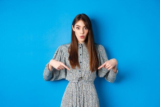 Opgewonden mooie vrouw in jurk zegt wow, wijzende vingers naar beneden en kijk geamuseerd, promotie checkend, staande op blauw.