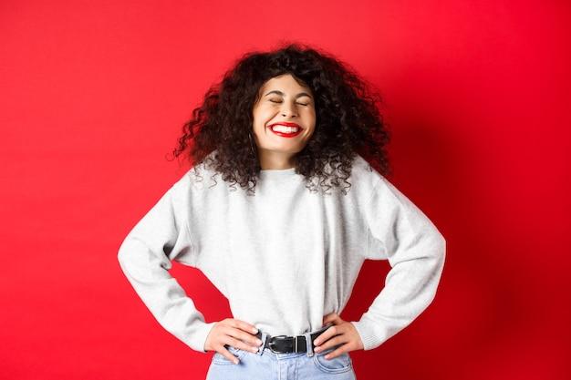 Opgewonden mooie vrouw lachen en glimlachen zorgeloos genieten van het leven staande in sweatshirt tegen r...