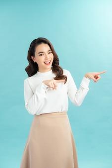 Opgewonden mooie vrouw staat zijwaarts met wijsvingers opzij op lege kopieerruimte voor uw advertentie of promotionele tekst.