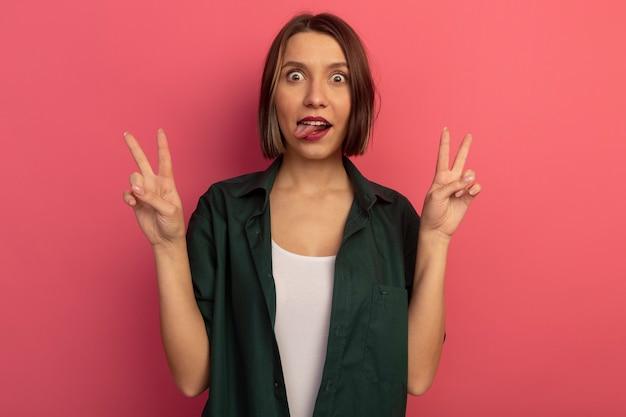 Opgewonden mooie vrouw steekt tong uit en gebaren overwinningsteken met twee handen geïsoleerd op roze muur