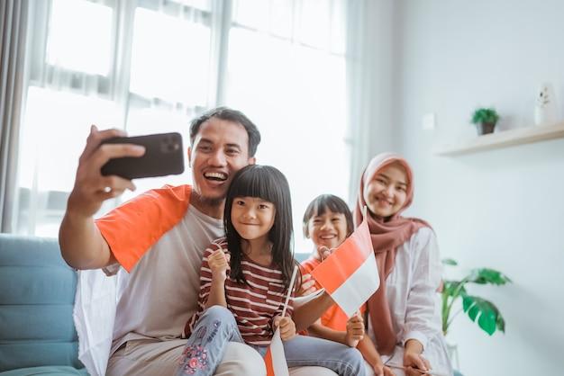 Opgewonden moslim-aziatische familie die selfie en videogesprek voert met hun telefoon thuis terwijl ze de indonesische vlag vasthouden