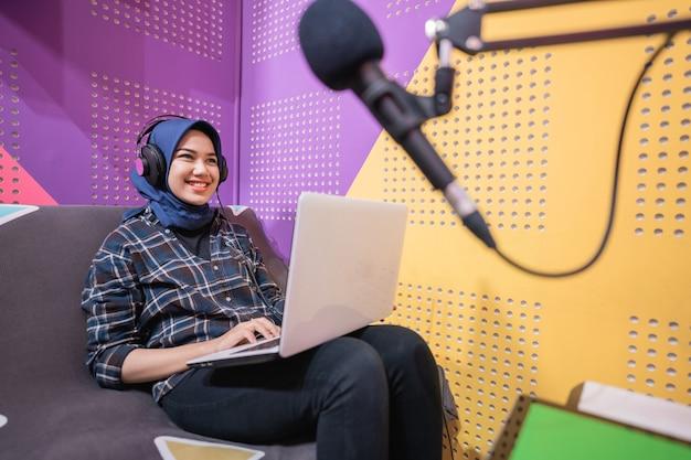 Opgewonden moslimvrouw neemt een podcast op in de studio met laptop