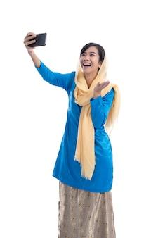 Opgewonden moslimvrouw videogesprekken met behulp van mobiele smartphone geïsoleerd over wit