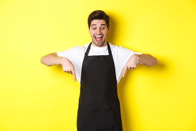 Opgewonden ober in zwart schort wijzende vingers naar beneden, promo-aanbieding uitchecken, staande op gele achtergrond.