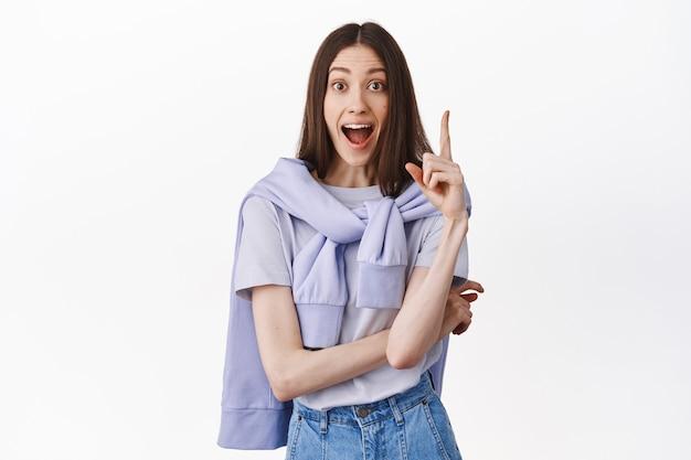 Opgewonden, opgewonden brunette meisje schreeuwt terwijl ze de vinger in het eureka-teken steekt, een geweldig plan heeft, een oplossing bedenkt, haar suggestie zegt, over een witte muur staat