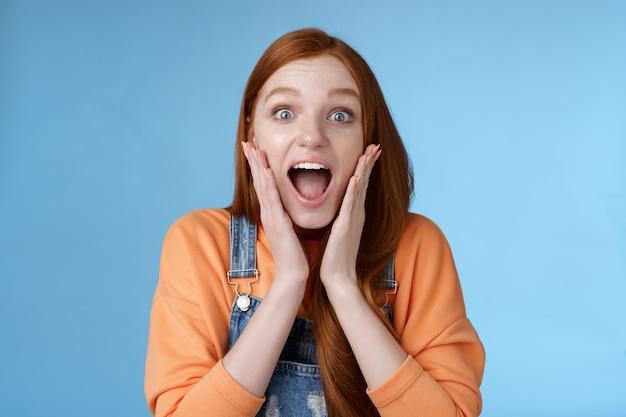 Opgewonden opgewonden jong emotioneel enthousiast rood meisje tiener student schreeuwen geamuseerd glimlachen breed ontvangen positief goed nieuws kijk verbaasd camera aanraking gezicht verbaasd blauwe achtergrond