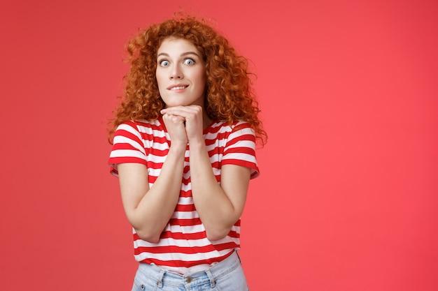 Opgewonden opgewonden jonge impulsieve knappe roodharige vrouw staren camera uitdrukken verlangen aspiratie lachend gek hand in hand kin ingedrukt houden zichzelf bij elkaar wil iets gretig eten.