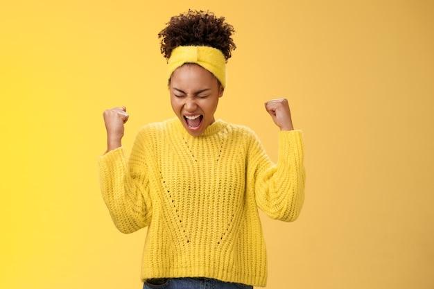 Opgewonden opgewonden mooie jonge studente schreeuwen gelukkig balde vuisten overwinning triomf pose dansen vieren acceptatie populaire universiteit staande tevreden doel bereiken droom die uitkomt.