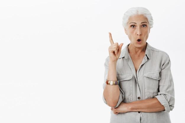 Opgewonden oudere moeder die vinger eureka-gebaar opheft, heeft idee, denkplan