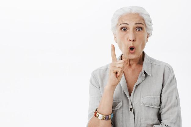 Opgewonden oudere vrouw heeft idee, wijsvinger eureka gebaar opheffen, plan voorstellen