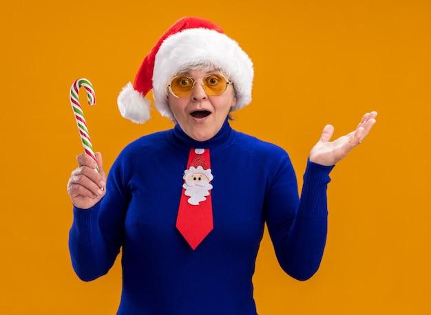 Opgewonden oudere vrouw in zonnebril met kerstmuts en kerststropdas houdt snoepgoed vast en houdt hand open geïsoleerd op oranje muur met kopieerruimte