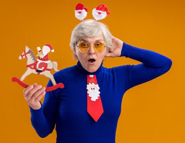 Opgewonden oudere vrouw in zonnebril met santa hoofdband en santa stropdas santa houden op hobbelpaard decoratie geïsoleerd op een oranje achtergrond met kopie ruimte