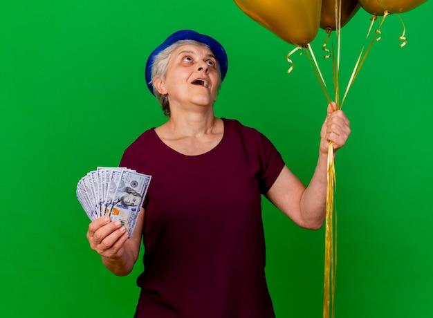 Opgewonden oudere vrouw met feestmuts houdt geld vast en kijkt naar helium ballonnen op groen