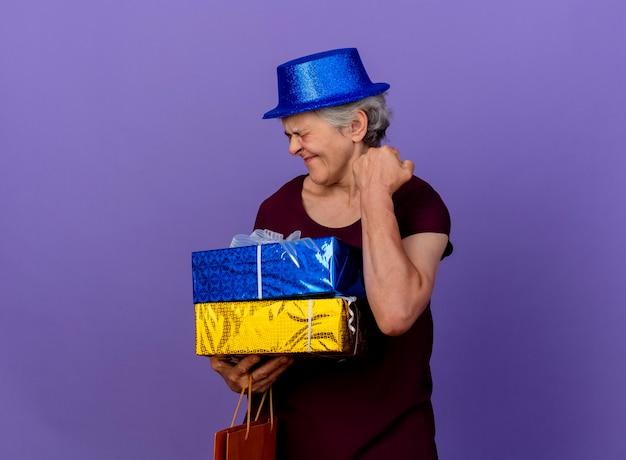 Opgewonden oudere vrouw met feestmuts houdt geschenkdozen en houdt vuist geïsoleerd op paarse muur met kopie ruimte