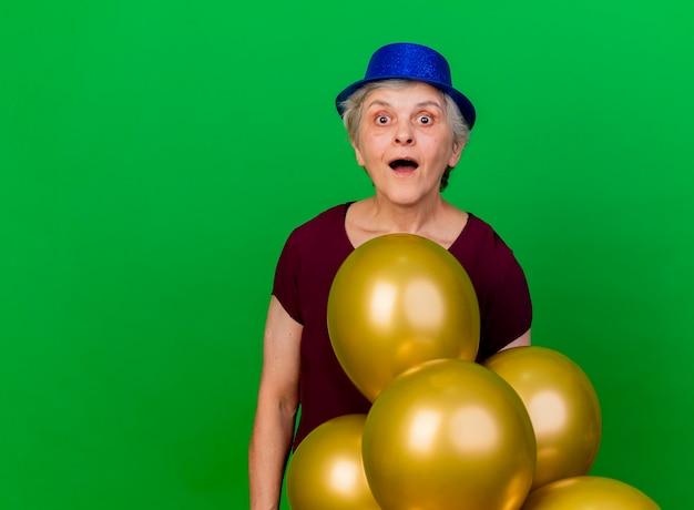 Opgewonden oudere vrouw met feestmuts staat met helium ballonnen op groen