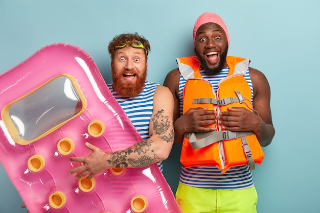 Opgewonden overemotive vrienden poseren met strandartikelen