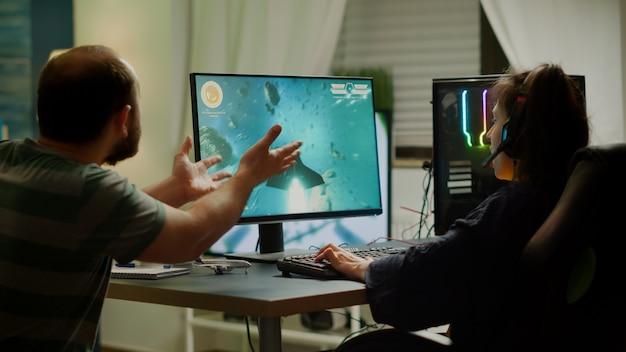 Opgewonden paar spelers winnen space shooter-videogame tijdens virtueel competitietoernooi met professionele headset. opgewonden online streaming-cybers die gamen met een krachtige rgb-computer