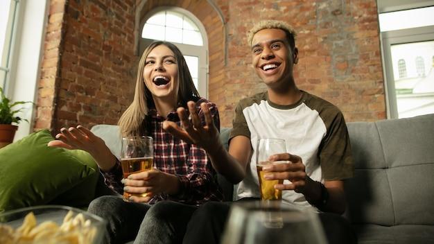 Opgewonden paar vrienden kijken naar sportwedstrijdkampioenschap thuis