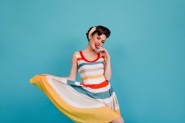 Opgewonden pinupmeisje speelt met gestreepte jurk. studio shot van lachende vrouw dansen op blauwe achtergrond.