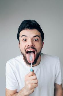 Opgewonden positieve kerel poseren. toon tong met tandenborstel en tandpasta erop. gezondheidszorg concept. orale tandheelkundige behandeling