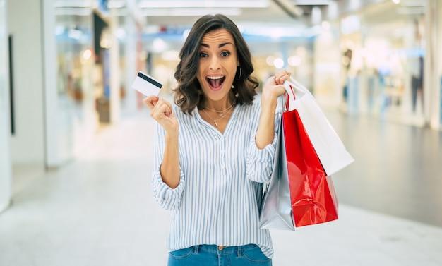 Opgewonden prachtige lachende jonge vrouw is poseren met een creditcard en boodschappentassen in het winkelcentrum