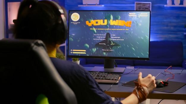 Opgewonden pro-gamer met professionele koptelefoon die een winnaargebaar maakt tijdens het spelen van space shooter-videogames
