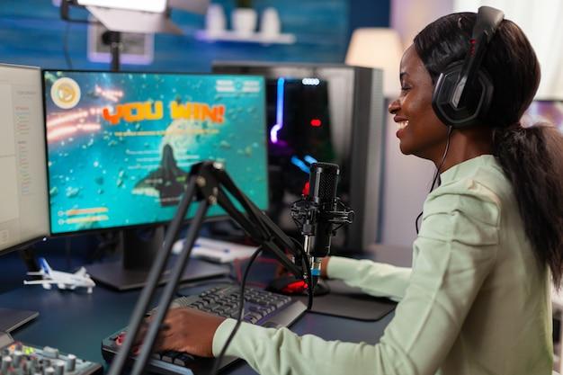 Opgewonden professionele afrikaanse e-sporter tijdens videogamestream van competitie na het winnen. online streaming cyber optreden tijdens videogametoernooi in huis met neonlichten.