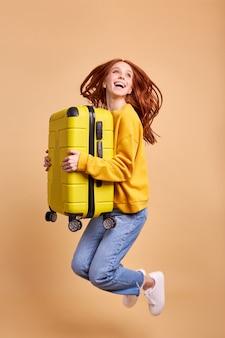 Opgewonden reiziger toeristische roodharige vrouw met koffer springen in casual outfit geïsoleerd in studio ...