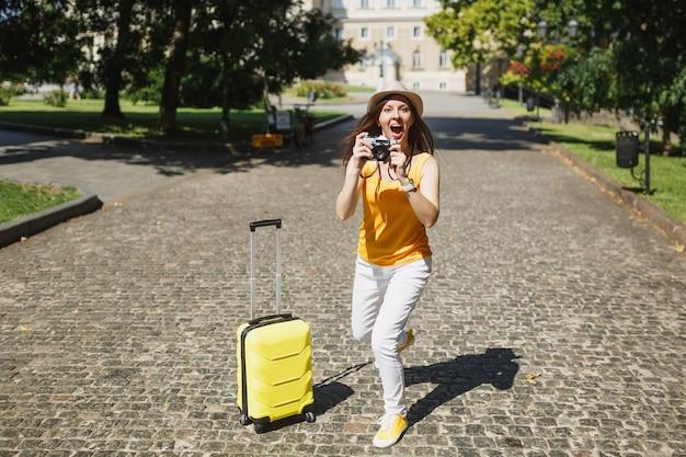 Opgewonden reiziger toeristische vrouw in gele casual kleding met koffer foto's maken op retro vintage fotocamera die buiten loopt. meisje op weekendje weg naar het buitenland. toeristische reis levensstijl.