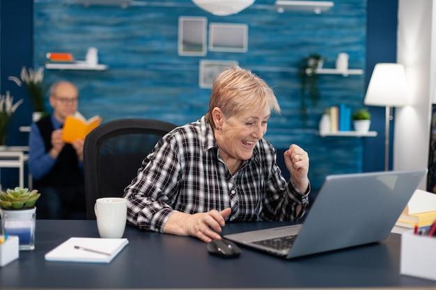 Opgewonden rijpe vrouw die online aankoop viert