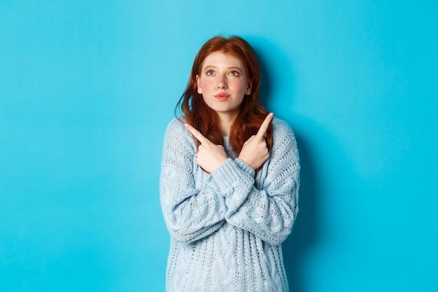Opgewonden roodharig meisje wijzend vingers zijwaarts, twee keuzes laten zien en verleidelijk kijken, staande tegen een blauwe achtergrond